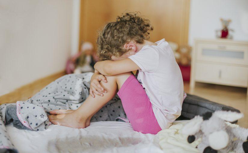 Bettnässen - ein trauriges Mädchen sitzt auf dem nassen Bett