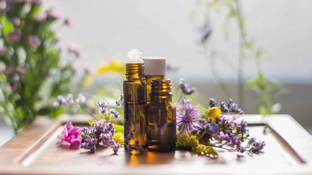 Drei Glässchen mit Ätherischen Ölen auf dem Tisch voller Blumen