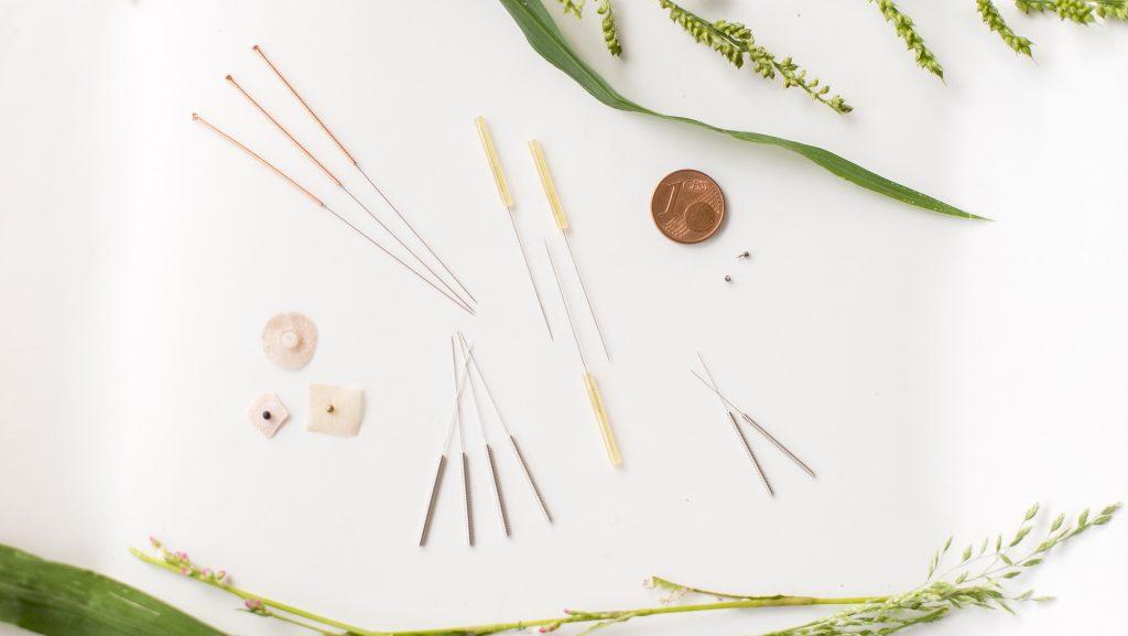 Unterschiedliche Akupunkturnadel und Akupunkturkügelchen sind am Tisch ausgelegt. Sie sehen winzig im Vergleich zu 5-Cent Münze aus.