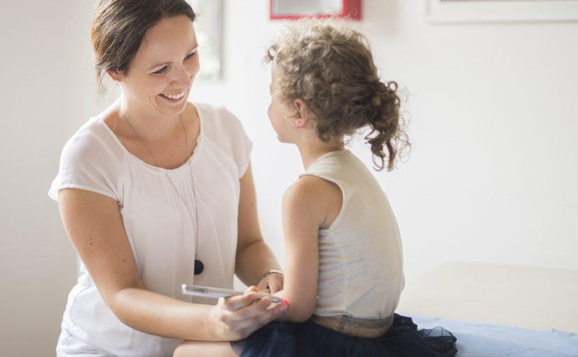 Ein Mädchen unterhält sich mit der Frau Dr. Schönhart, während sie eine schmerzfreie Laserakupunktur bekommt