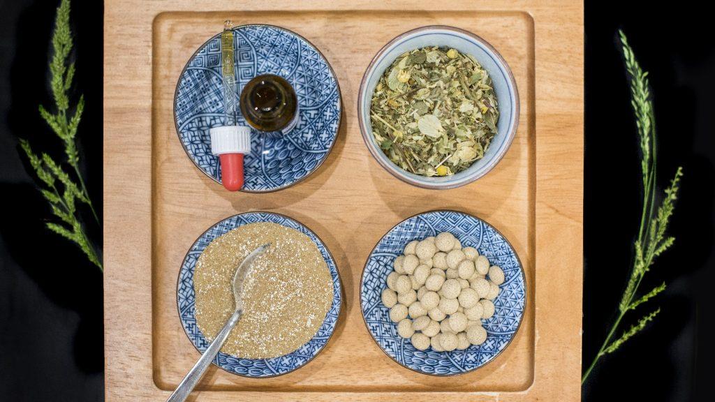 Vier Teller mit Chinesischen Arzneimitteln und Kräutern stehen auf dem Holzbrett