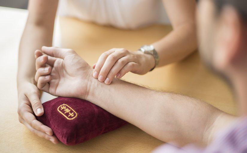 Ein Mann streckt sein Arm aus. Frau Dr. Schönhart spürt sein Puls auf um eine Pulsdiagnostik durchzuführen